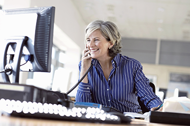 Mature woman using telephone at desk in office